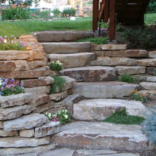 Photo of a large traditional shade backyard stone retaining wall landscape in New York.