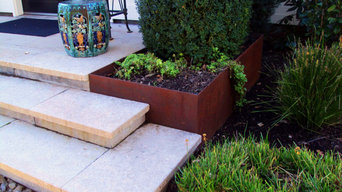 Stone veneered stairs designed to accommodate fabricated corten planter