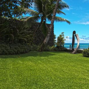 Inspiration för stora exotiska bakgårdar, med en stödmur och naturstensplattor