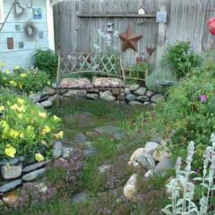 Inspiration pour un petit jardin arrière style shabby chic l'été avec une exposition ensoleillée et des pavés en pierre naturelle.
