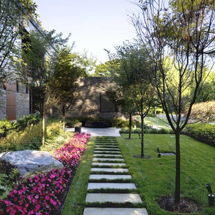 Inspiration for a large traditional side partial sun garden in New York with natural stone paving.