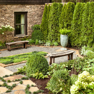 Design ideas for an expansive traditional backyard garden in Other with gravel.