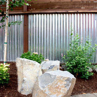 Inspiration for a mid-sized modern full sun backyard stone landscaping in Portland.