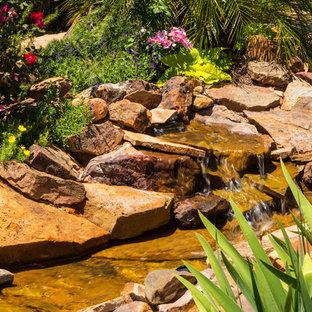 Immagine di un grande giardino country esposto in pieno sole dietro casa con pavimentazioni in pietra naturale