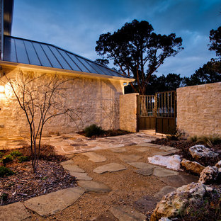 Design ideas for a large traditional side yard full sun xeriscape for winter in Dallas with natural stone pavers and a retaining wall.