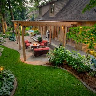 Réalisation d'un grand jardin arrière tradition avec des pavés en pierre naturelle et des bordures.