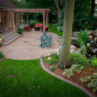 Exemple d'un grand jardin arrière chic avec des pavés en pierre naturelle et des bordures.
