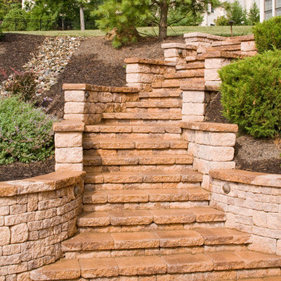 Photo of a mid-sized traditional partial sun hillside concrete paver formal garden in Philadelphia for spring.
