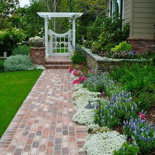 Imagen de jardín parterre de flores, tradicional, en patio lateral, con exposición total al sol y adoquines de ladrillo