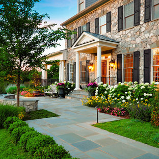 Design ideas for an expansive traditional front yard partial sun formal garden for spring in DC Metro with concrete pavers.