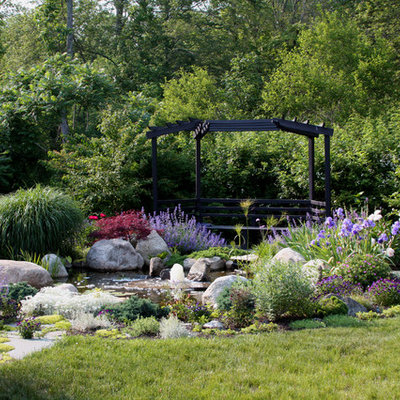 This is an example of a traditional backyard stone water fountain landscape in Boston for summer.