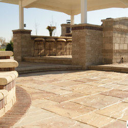 Hardscape - Multi-level brick patio with a tiered retaining wall and a covered bar and grill.