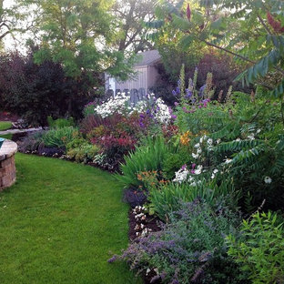 Inspiration for a mid-sized traditional partial sun backyard mulch landscaping in Other for summer.