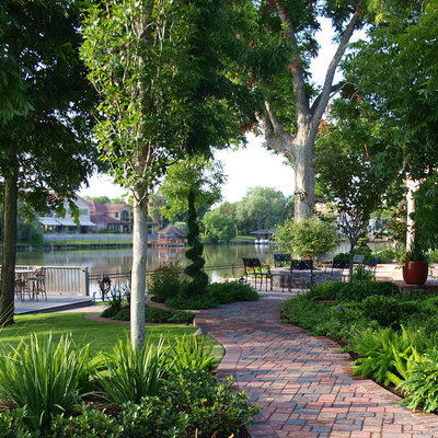 Inspiration for a huge traditional partial sun hillside brick garden path in Houston.