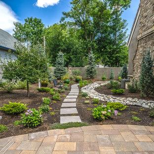 Aménagement d'un grand jardin à la française latéral classique l'été avec des pavés en béton, une exposition partiellement ombragée et des solutions pour vis-à-vis.