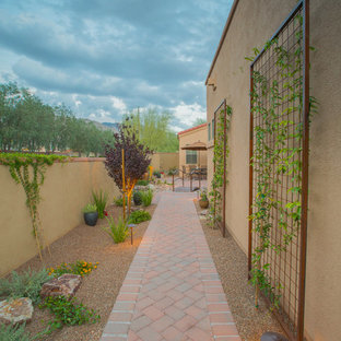 This is an example of a mid-sized southwestern drought-tolerant, partial sun and desert side yard brick landscaping in Phoenix.
