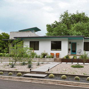 This is an example of a mid-sized midcentury modern drought-tolerant and full sun front yard gravel landscaping in Austin.