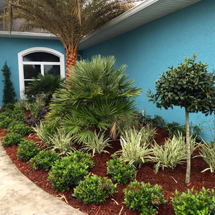 Photo of a large traditional partial sun backyard brick landscaping in Orlando.