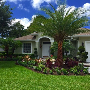 Inspiration for a large tropical partial sun backyard brick landscaping in Orlando.