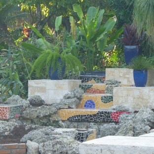 Photo of a modern partial sun backyard stone water fountain landscape in Miami.