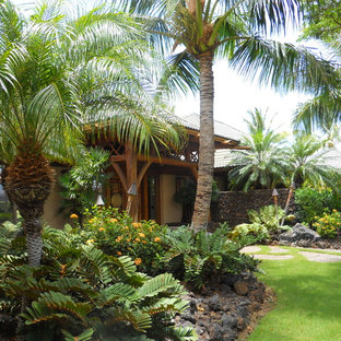 Inspiration for a mid-sized tropical partial sun front yard stone landscaping in Hawaii.