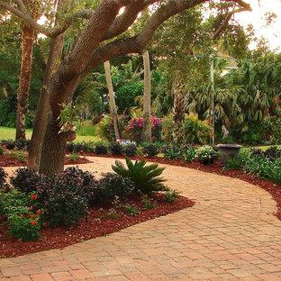 Ejemplo de jardín clásico, de tamaño medio, con exposición parcial al sol y adoquines de ladrillo