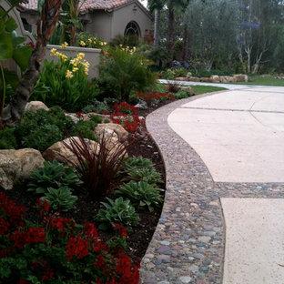 Неиссякаемый источник вдохновения для домашнего уюта: большой солнечный участок и сад на переднем дворе в средиземноморском стиле с подъездной дорогой, хорошей освещенностью и покрытием из каменной брусчатки