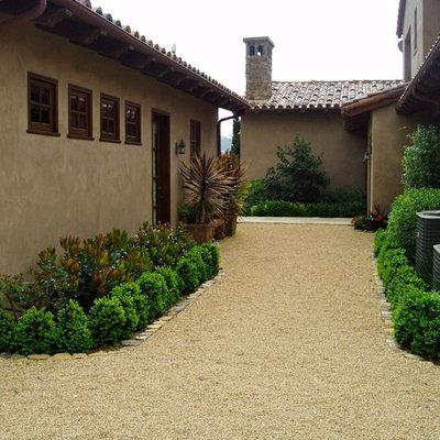 Inspiration for a large mediterranean full sun backyard gravel landscaping in San Diego.