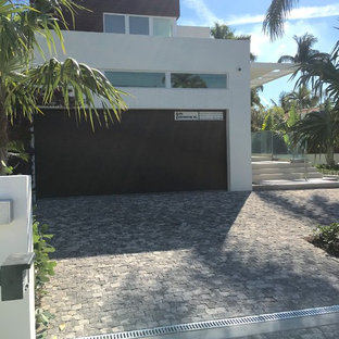 Photo of a mid-sized tropical partial sun front yard concrete paver landscaping in Miami.