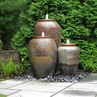 Imagen de jardín clásico, de tamaño medio, en verano, en patio trasero, con fuente, exposición total al sol y adoquines de piedra natural