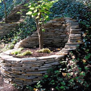 Inspiration för eklektiska trädgårdar, med en stödmur