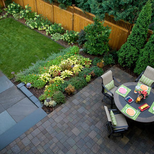 Traditional backyard garden in Minneapolis with natural stone pavers and a vegetable garden.