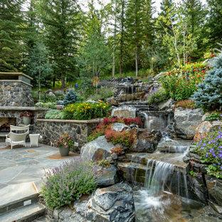 Aménagement d'un jardin classique au printemps avec une cascade, une exposition ensoleillée et des pavés en pierre naturelle.