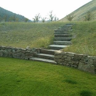 На фото: огромные солнечные участки и сады на склоне в стиле кантри с подпорной стенкой, освещенностью и покрытием из каменной брусчатки