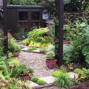 На фото: с невысоким бюджетом маленькие солнечные, летние засухоустойчивые растения на заднем дворе в средиземноморском стиле с хорошей освещенностью и покрытием из гравия