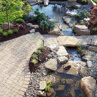 Cette image montre un grand jardin arrière traditionnel avec un point d'eau et des pavés en brique.