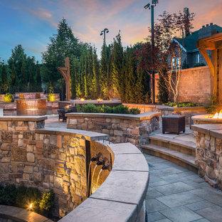 Idées déco pour un grand jardin arrière montagne avec des pavés en béton et un foyer extérieur.