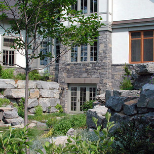Photo of a large farmhouse full sun backyard stone retaining wall landscape in New York for spring.