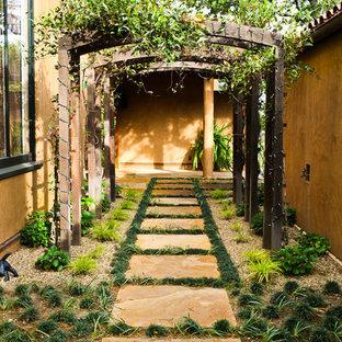 Ejemplo de jardín francés, mediterráneo, de tamaño medio, con exposición parcial al sol y adoquines de piedra natural