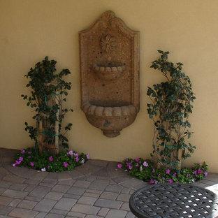 Diseño de jardín clásico, de tamaño medio, en patio trasero, con fuente