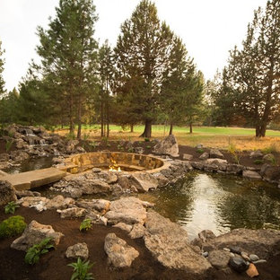 Photo of a large craftsman full sun backyard stone pond in Other.