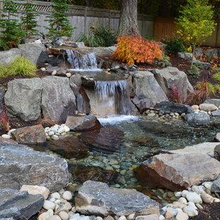 Klassischer Garten hinter dem Haus mit Wasserspiel und Flusssteinen in Seattle