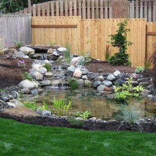 Réalisation d'un grand jardin arrière tradition avec un bassin, une exposition ensoleillée et un paillis.