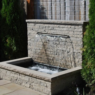 Small traditional backyard full sun garden in Toronto with a water feature and concrete pavers for spring.
