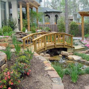 Foto di un grande giardino chic esposto a mezz'ombra dietro casa in primavera con fontane e pavimentazioni in pietra naturale