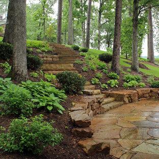 Cette image montre un jardin marin de taille moyenne et au printemps avec une pente, une colline ou un talus, des pavés en pierre naturelle, un mur de soutènement et une exposition partiellement ombragée.