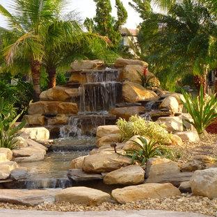 Idéer för en mellanstor exotisk bakgård i full sol, med en fontän och naturstensplattor
