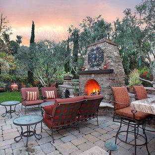 Cette image montre un jardin à la française latéral méditerranéen de taille moyenne et l'hiver avec un foyer extérieur, une exposition partiellement ombragée et des pavés en pierre naturelle.
