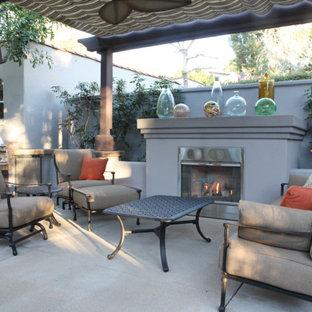 Halbschattiger Klassischer Garten hinter dem Haus, im Winter mit Betonplatten und Kamin in Los Angeles