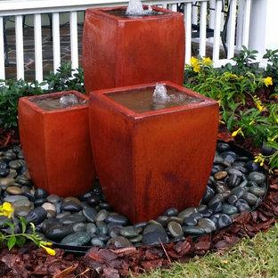 Idee per un giardino formale tropicale esposto in pieno sole di medie dimensioni e davanti casa con fontane e pavimentazioni in mattoni
